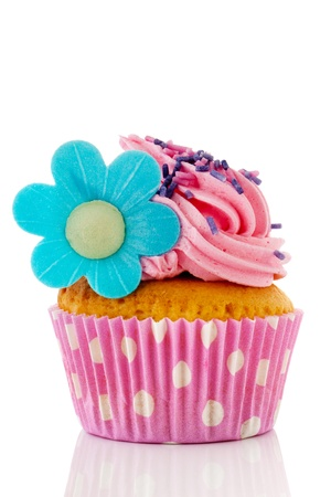 cupcakes isolated: Pink cupcake with sprinkles and blue flower isolated over white background