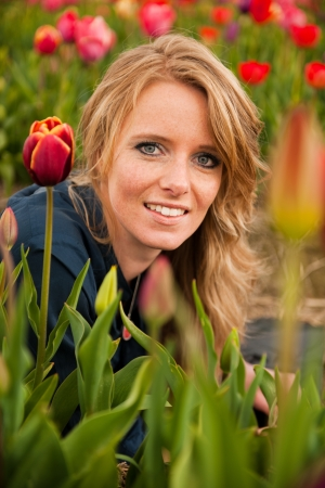 dutch girl: Portrait of a beautiful blond Dutch girl in tulips field Stock Photo