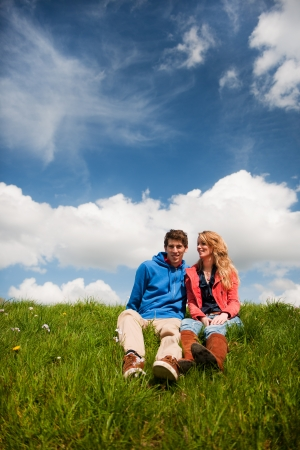 dike: Young couple sitting in nature grass landscape