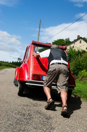 Typical French man is pushing his car after a breakdown photo
