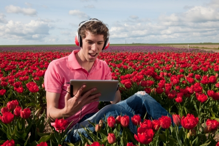 man in Dutch landscape is listening to the digital tablet PC photo