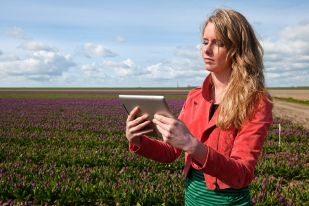 Dutch girl with long blond hair and digital tablet PC in flower fields photo