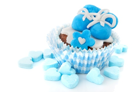 Blue cupcake with baby shoes and candy hearts photo