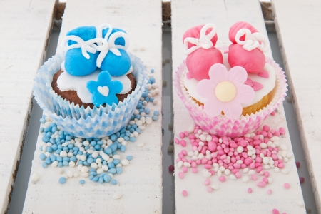 Pink cupcake with baby shoes and hearts in pink and blue photo
