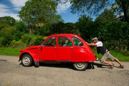 Typisch Französisch Mann schiebt sein Auto nach einer Panne