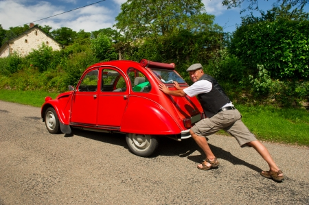 Typical French man is pushing his car after a breakdown Stock Photo