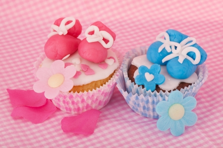 sugar paste: Pink and blue cupcake with baby shoes and hearts Stock Photo