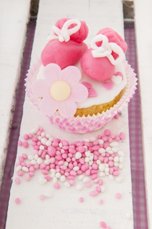 Pink cupcake with baby shoes and candy photo