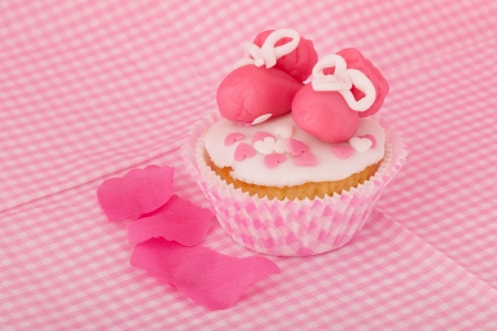 Pink cupcake with baby shoes and hearts photo