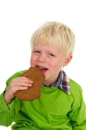 speculaas: Little child is eating Dutch chocolate Sinterklaas speculaas puppet