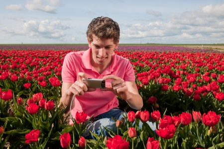 Portrait of an young man taking pictures in tulips field with photo camera photo