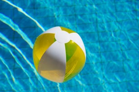beachball: Inflatable yellow beachball floating at the water