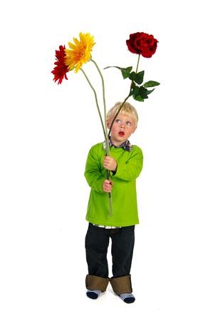 Portrait of a little blond boy carrying big flowers photo