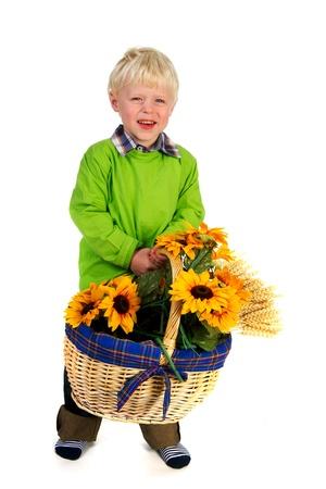 Portrait of a little blond boy carrying a flower basket photo
