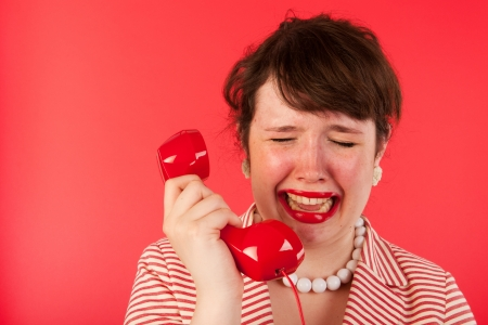 layoffs: Young woman on red is crying on the telephone Stock Photo