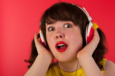 Young girl is listening music with headphones on red Stock Photo - 14697799