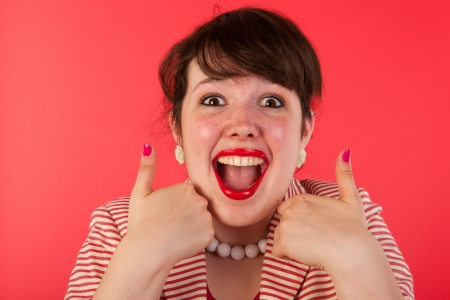 Young woman is having thumbs up on red Stock Photo - 14697800
