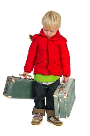 Little boy with suitcases and coat is walking away from home photo