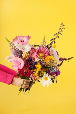 Holding mixed garden bouquet flowers on yellow background photo