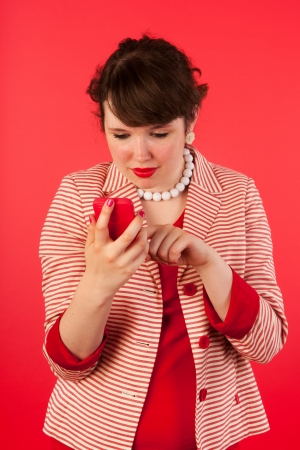 Young woman on red with smart phone Stock Photo - 14939906