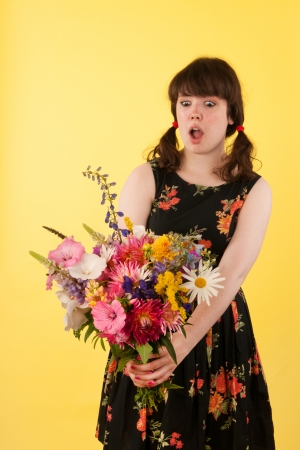 Young woman is surprised with bouquet colorful garden flowers photo
