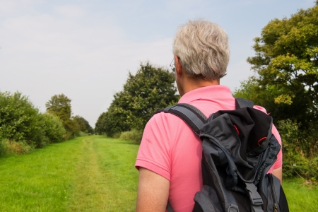 plassen: Senior man is hiking in nature