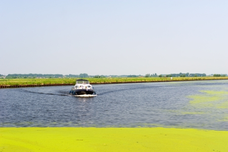 eem: Little motorboat on Dutch river the Eem in the Netherlands
