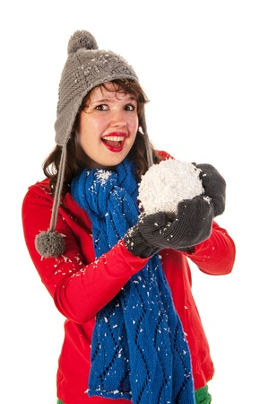 Winter girl in red and blue is throwing snow ball