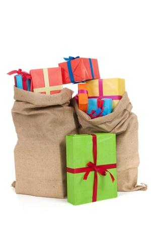 vele kleurrijke presenteert met luxe linten in jute zakken geïsoleerd op witte achtergrond Stockfoto