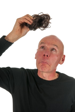 hairpiece: Bald man is looking at his hair