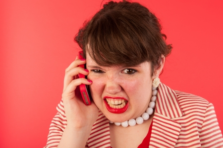 Young woman is having an angry phone call at the smartphone photo
