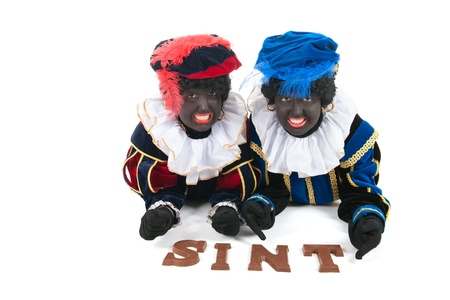 Dutch characters as black petes for typical Sinterklaas holidays laying with chocolate letters photo