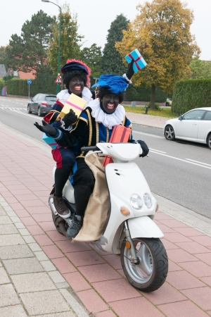 petes: Dutch characters as black petes for typical Sinterklaas holidays riding on scooter with presents