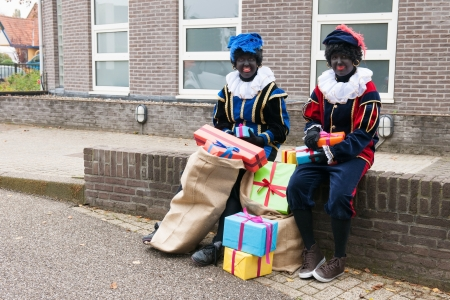 pieten: Dutch characters as black petes for typical Sinterklaas holidays sitting outdoor with presents Stock Photo