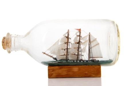 Oude zeilboot in glazen fles geà ¯ soleerd op witte achtergrond Stockfoto