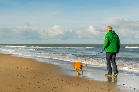 年配の男性人は、ビーチで犬を散歩します。