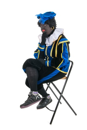 Black pete for typical Sinterklaas holidays sitting on chair and thinking photo
