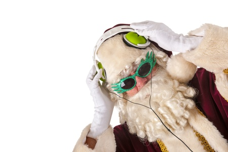 Portrait of Santa Claus listening to cool music with copy space photo