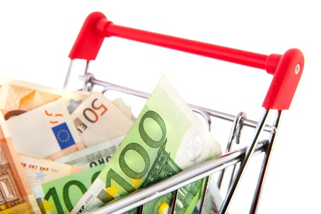 Expensive shopping cart with euro banknotes in different values isolated over white background photo