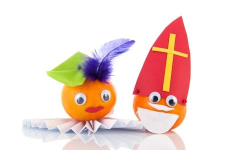 Nederlandse Sinterklaas en Zwarte Piet als mandarijnen geà ¯ soleerde over witte achtergrond