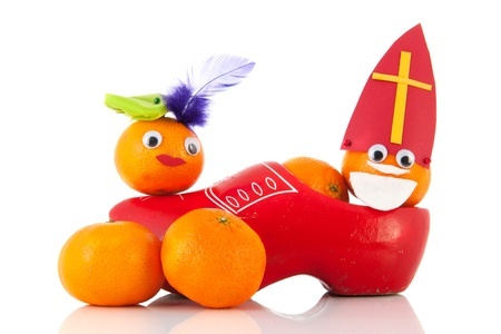 mandarins: Dutch Sinterklaas and Black Pete as mandarins in red clog isolated over white background