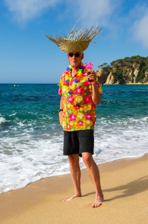 Senior man with cocktail drink at the tropical beach photo