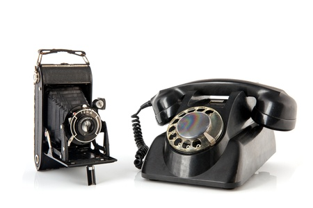 Old black photo camera and black telephone isolated over white background Stock Photo - 17171286