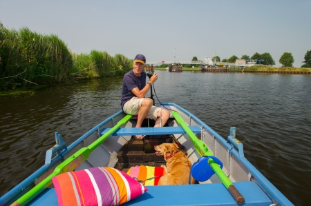 eem: Senior man with dog in little rowingboat at Dutch river Stock Photo