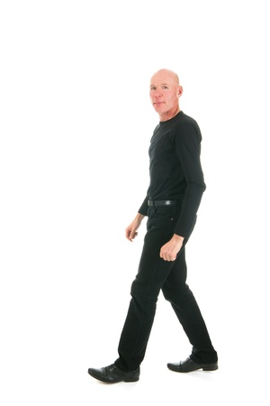 sidewards: Adult bald man dressed in black walking in the studio Stock Photo