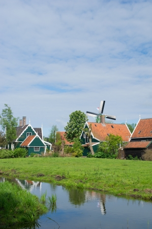 Typical Dutch village with green wooden houses and windmill photo