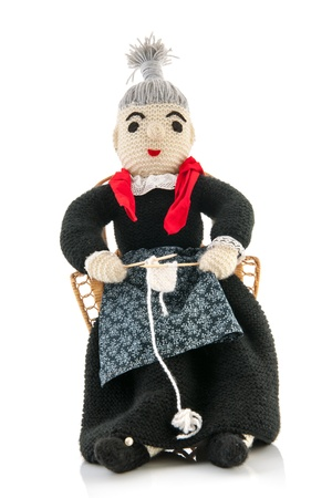 hand knitted grandma sitting on chair and knitting photo