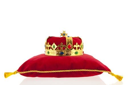 Golden crown on red velvet pillow for coronation photo