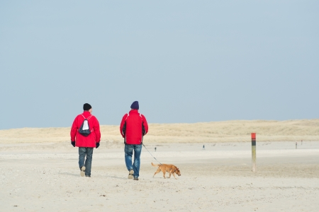 Two man with dog are hiking at the coast photo