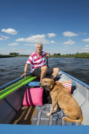 Man with dog in boat at the river photo
